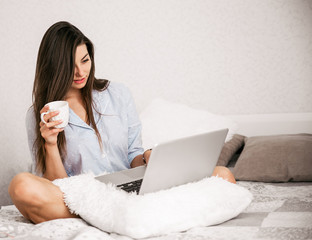 Young smiling woman working on laptop in her bedroom. Happy morning.