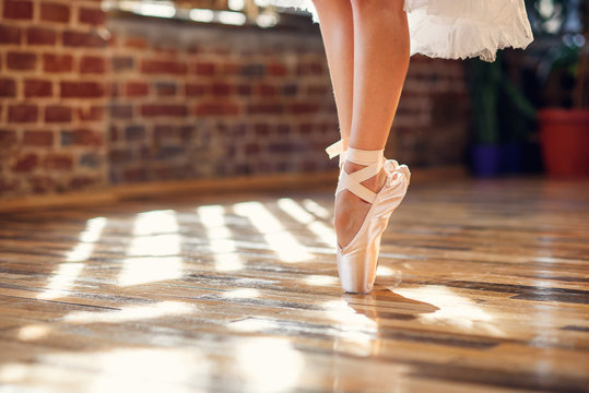Close-up dancing legs of ballerina wearing white pointe ballet shoes in the dancing hall.