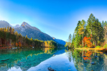 Beautiful autumn sunrise scene with trees near turquoise water of Hintersee lake