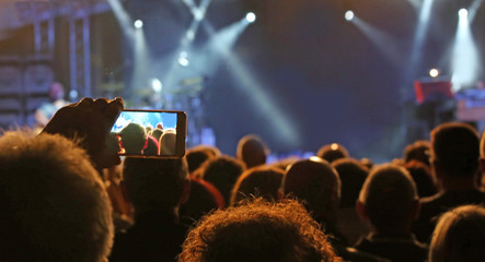 person with smartphone while recording a movie during a concert