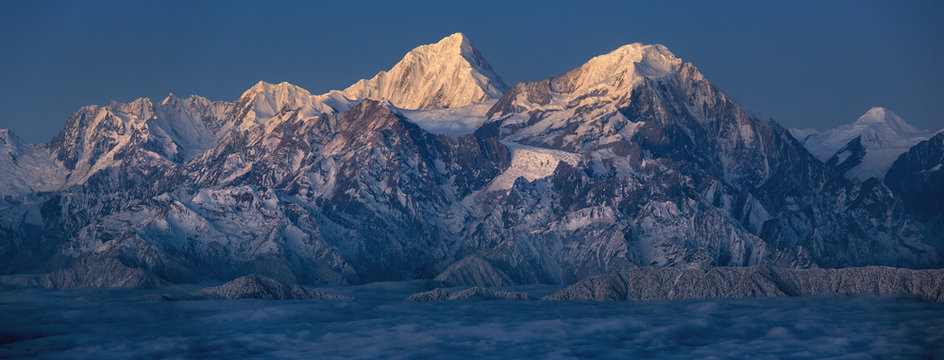 Minya Konka (Mount Gongga) view from Niubeishan Cattle Back Mountain in Sichuan Province, China. Summit shrouded in clouds. Highest Mountain in Sichuan Province China. Twilight moonlit landscape
