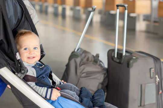 Cute funny caucasian baby boy sitting in stroller near luggage at airport terminal. Child sin carriage with suitcasese near check-in desk counter. Travelling with small children concept