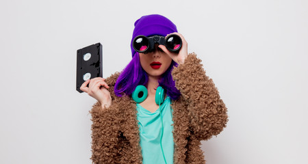Beautiful young girl with purple hair in jacket holding VHS cassette and binocular on white background.
