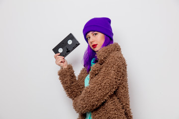 Beautiful young girl with purple hair in jacket holding VHS cassette on white background.
