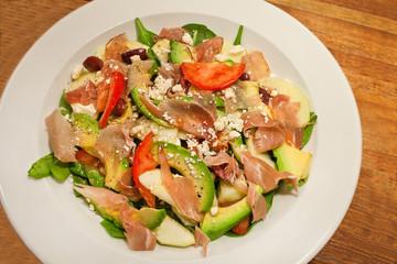 Mixed summer salad with avocado, ham and tomato