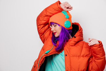 Beautiful young girl with purple hair and in orange jacket listen music in headphones on white background.