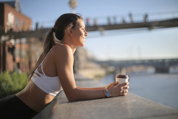 Sportive girl resting drinking a coffee and looking at the view