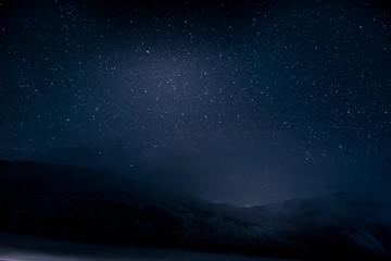 Beautiful blue dark night sky with many stars above snowy mountains
