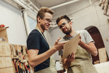 Two young men in aprons and goggles smiling and pointing at papers while working in modern joinery together Wall mural
