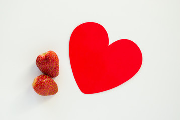 Valentine's Day-two ripe red strawberries with a red paper heart isolated on white