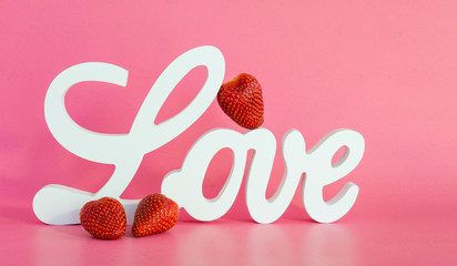 Valentine's Day-white wooden letters spelling the word LOVE with a ripe red strawberry leaning against the L and two strawberries in front isolated on a pink background