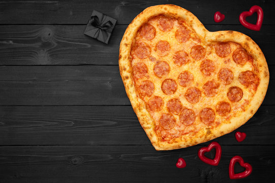 Pizza heart for Valentine's Day with copy space on rustic dark black background. Top View. Flat lay