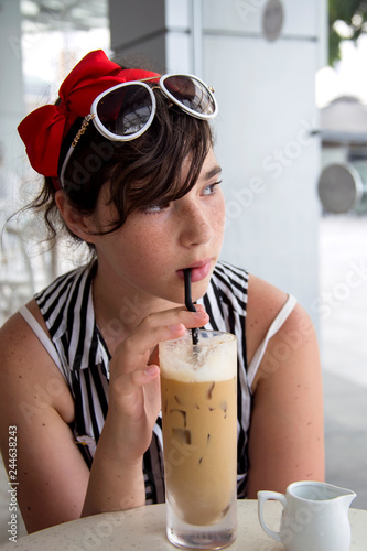 1a0606c89632 A teenage girl with pretty freckles on her face, drinks ice coffee through  a straw in a cafe near the window.