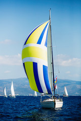 Wall Mural - Luxury yacht with color sails at Regatta. Sailing in the wind through the waves at the Sea.