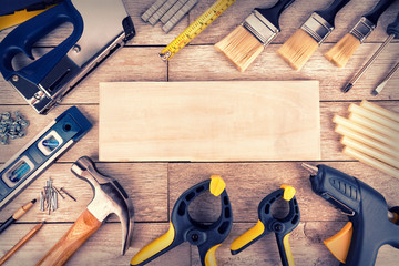 Set of construction tools on a white wooden plank, directly above. Copy space for your text.