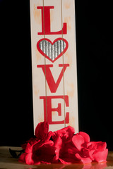 Wooden sign with the word LOVE appearing with an abundance of red roses.