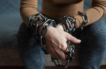 Woman's hands in chains. Lack of freedom