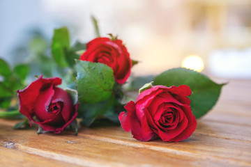 Red roses flower on wooden table with blur background