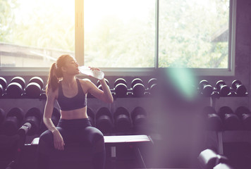 Attractive woman sitting and drinking water in gym,Asian female break and relex after workout