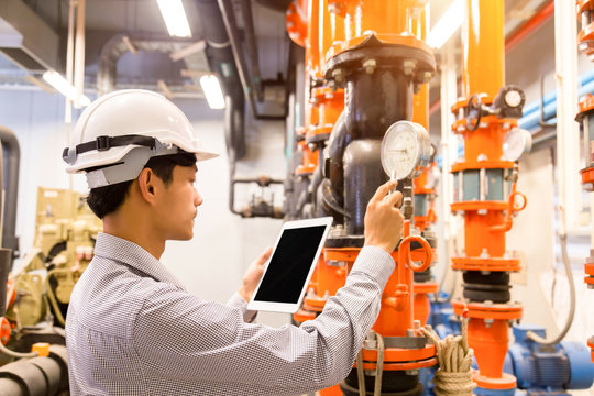 Asian engineer maintenance checking technical data of  system equipment Condenser Water pump and pressure gauge , chiller water pump with pressure gauge.