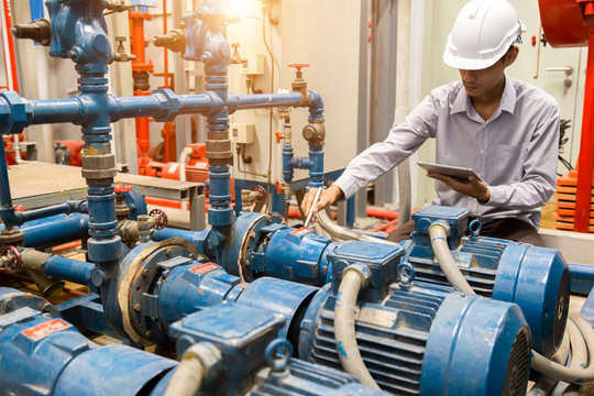 Asian engineer maintenance checking technical data of  system equipment Condenser Water pump and pressure gauge ,  water pump.