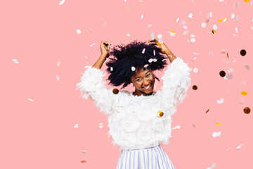 Portrait of a very happy young woman with black curly hair dancing amidst confetti falling