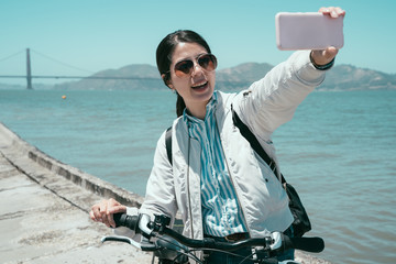 Happy young female tourist taking selfie