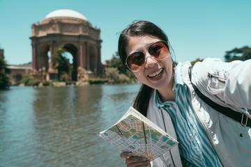 female tourist taking selfie holding paper map