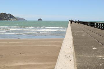 People having fun on the pier in Tolaga Bay, New Zealand.