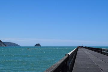 Summer fun at the beach along the pier in Tolaga Bay, New Zealand.