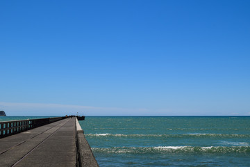 Scenic shot showing the length of the pier against the blue sea in Tolaga Bay, New Zealand.