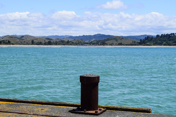 Rusty post at the end of the very long wharf in Tolaga Bay, New Zealand.