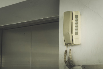 Dial the emergency analog telephone hanging on the wall at the elevator., with copy space for text.