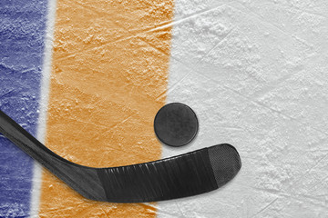 Hockey stick, puck and ice arena fragment with blue and orange lines