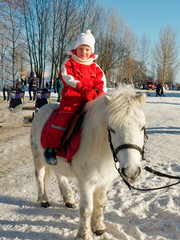 child riding a pony outside in winter.