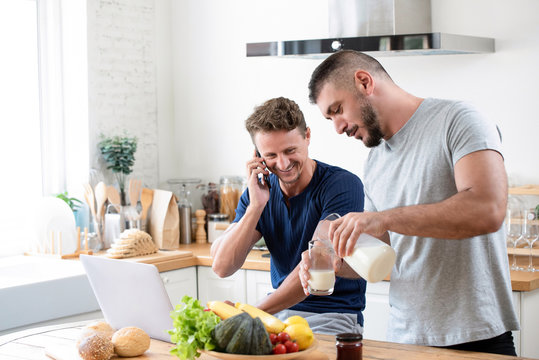 Happy gay male preparing breakfast for his partner at home