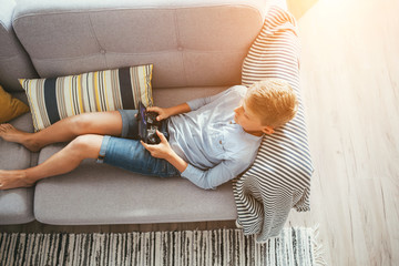 Boy laying on sofa plays with electronic devices - gamepad connected with smartphone