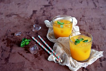 Refreshing drink, orange juice with basil in glasses. Served with ice cubes and a straw.