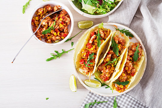 Mexican tacos with chicken meat, corn and tomato sauce. Latin American cuisine. Taco, tortilla, wrap. Top view. Flat lay