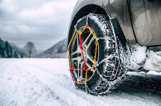 Snow chains on tire at winter road