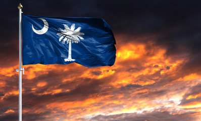 flag State of South Carolina on flagpole fluttering in the wind against a colorful sunset sky