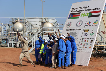 Workers take a photo during a ceremony marking the restarting of crude oil pumping at the Unity oil fields