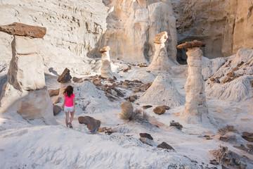 A hiker walking among hoodoos sandstone formations in Utah, USA