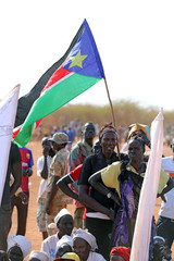 Women hold the South Sudanese flag during a ceremony marking the restarting of crude oil pumping at the Unity oil fields