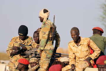 Armed members of the South Sudanese security forces are seen during a ceremony marking the restarting of crude oil pumping at the Unity oil fields