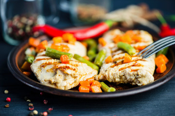 grilled turkey fillet with vegetables, pepper and spices on a plate