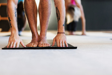 close up Group of young people who love yoga make anasa standing on the floor mats in a cozy little room. Concept of relieving fatigue and the beneficial effects on the abdominal organs