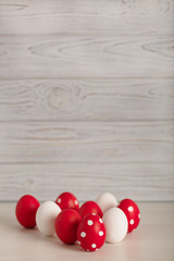 Happy Easter! Painted Easter eggs - red, white and red with white polka dots on a gray wooden background.