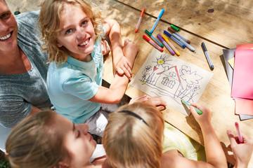 Kinder malen ein Eigenheim mit Buntstiften