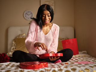 african american woman excited to try romantic valentines day chocolates out of heart shaped giftbox